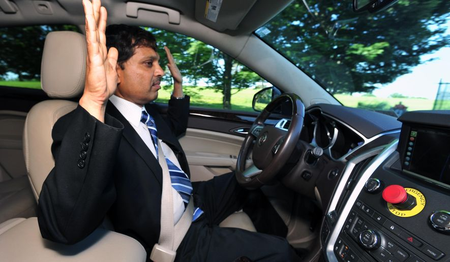 Raj Rajkumar, professor of engineering at Carnegie Mellon University, drives the autonomous vehicle down Schenley Drive in Schenley Park in Pittsburgh, on June 1, 2016. The university has been working on a self-driving vehicle for nearly three decades, but the effort kicked into high gear in February 2015 when Uber announced it would partner with CMU's National Robotics Engineering Center.   (Nate Guidry/Pittsburgh Post-Gazette via AP) MAGS OUT; MONESSEN OUT; KITTANNING OUT; CONNELLSVILLE OUT; GREENSBURG OUT; TARENTUM OUT; NORTH HILLS NEWS RECORD OUT; BUTLER OUT; MANDATORY CREDIT