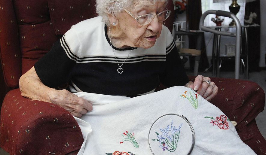 In this April 18, 2016 photo, Helen Swick checks the stitching on a floral embroidery project at her home in Bloomington, Ill. On May 8, 2016, the Swick family had more to celebrate than Mother's Day. The day also marked Helen's 102nd birthday. (Lori Ann Cook-Neisler/The Pantagraph via AP)  MANDATORY CREDIT