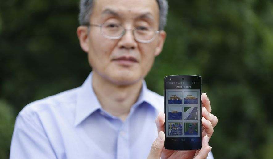 ADVANCE FOR USE MONDAY, JUNE 6 - In this photo taken May 26, 2016, D.J. Seo, associate professor of civil engineering at University of Texas/Arlington, displays an Android phone app called iSeeFlood in Fort Worth, Texas. Seo has launched the crowdsourcing app that will allow real-time flooding to be reported. Initially, it will only be available on Android phones, but Seo hopes to raise enough funding to develop an Apple version of the app. (Rodger Mallison/Star-Telegram via AP)  MAGS OUT; (FORT WORTH WEEKLY, 360 WEST); INTERNET OUT; MANDATORY CREDIT