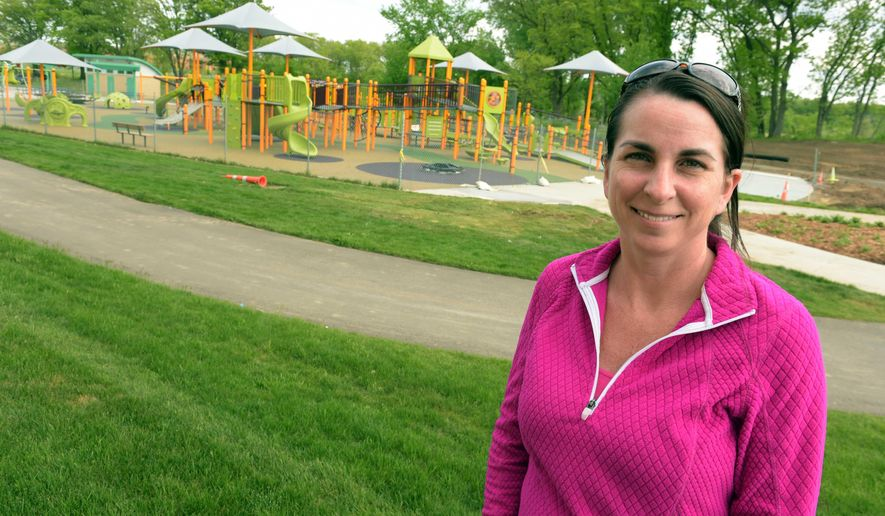 """ADVANCE FOR USE SATURDAY, JUNE 4, 2016, AND THEREAFTER- This May 19, 2016, photo Dana Millington poses for a photo by a playground named """"Madison's Place"""" that was built for children with disabilities in Woodbury, Minn. Millington, who, reached her goal of building the playground said she is naming it after her daughter Madison, who died when she was 2 years old of spinal atrophy. (Scott Takushi/Pioneer Press via AP)  MINNEAPOLIS STAR TRIBUNE OUT; MANDATORY CREDIT"""