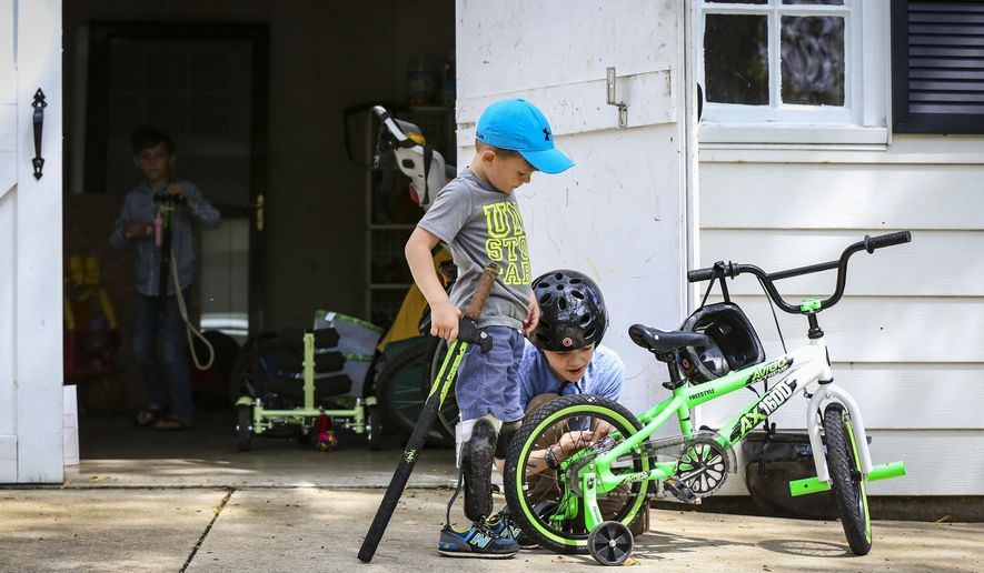 ADVANCE FOR USE SATURDAY, JUNE 4 AND THEREAFTER - In this May 8, 2016, photo, Jude Hill, left, watches as his brother Micah, tapes a card to his bike frame to give his bike a motorcycle sound while riding in their driveway in Peoria, Ill. A double amputee as a result of a lawnmower accident two years ago, Jude underwent a number of surgeries and two sets of feet on his journey to recovery with the support of his family. He now runs and plays like any other young boy. (Andy Abeyta/Journal Star via AP)  MANDATORY CREDIT