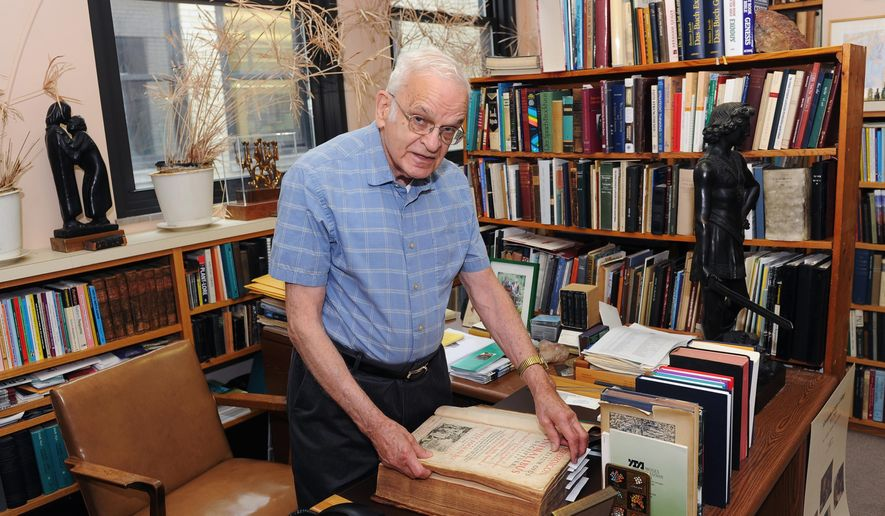 In this May 26, 2016 photo, Rabbi Walter Jacob, rabbi emeritus and senior scholar at Rodef Shalom Congregation views a Latin book on gardening inside his office in the Shadyside neighborhood of Pittsburgh. He's being honored as a pursuer of peace. (Nate Guidry/Pittsburgh Post-Gazette via AP) MAGS OUT; MONESSEN OUT; KITTANNING OUT; CONNELLSVILLE OUT; GREENSBURG OUT; TARENTUM OUT; NORTH HILLS NEWS RECORD OUT; BUTLER OUT; MANDATORY CREDIT