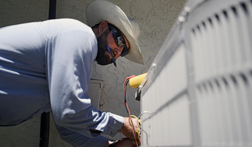 Josh Salow checks to see if an air conditioning unit is working at a home in Tempe, Ariz., on Thursday June 2, 2016. Salow said summer is the busiest season for AC repairs, and he fixes roughly three to four units a day in summer months. Parts of the Western U.S. are getting an early taste of scorching summer heat, forcing officials in California, Oregon and desert Southwest states to heed the warnings of dangerous, triple-digit temperatures in this first week of June.  (AP Photo/Beatriz Costa-Lima)