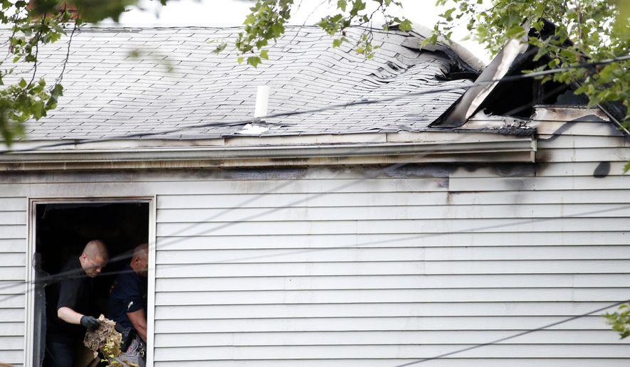 Investigators are seen through a window Thursday, June 2, 2016, where police say multiple people were found dead inside the home that had been ablaze, in Fair Lawn, N.J. According to Sgt. Brian Metzler, a neighbor reported the home was on fire late Wednesday night. (AP Photo/Julio Cortez)