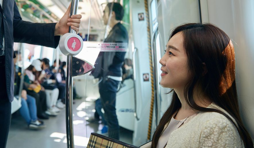 "In this Wednesday, April 6, 2016 photo provided by Busan Metropolitan City, a woman sits on special priority seats next to a metal bar attached with a ""pink light"" wireless sensor in a subway train in Busan, South Korea. South Korea's second-largest city of Busan is testing a wireless technology it hopes can alleviate such problems and perhaps help address one of the biggest challenges facing the Asian country: a stubbornly low birthrate. (Kwon Sung-hoon/Busan Metropolitan City via AP)"