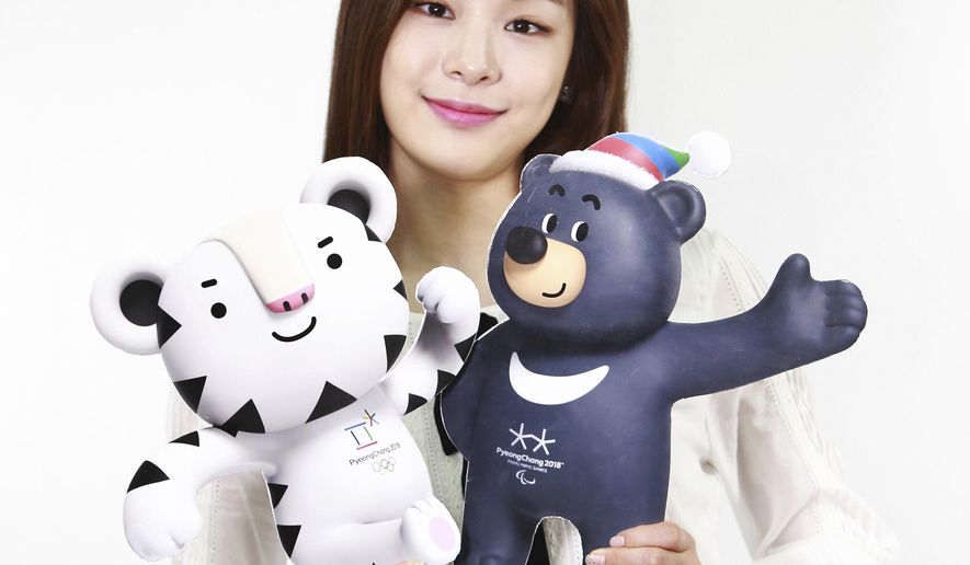 In this photo provided by the PyeongChang Organizing Committee for the 2018 Olympic & Paralympic Winter Games, a former South Korean Olympic figure skater Yuna Kim who is an honorary ambassador for the 2018 Winter Olympics, holds the cut-outs of the official mascots for the 2018 PyeongChang Olympics, named Soohorang, left, and Paralympic Winter Games, named Bandabi, right, in Seoul, South Korea, Thursday, June 2, 2016. (PyeongChang Organizing Committee for the 2018 Olympic & Paralympic Winter Games via AP) Editorial Only, No Commercial