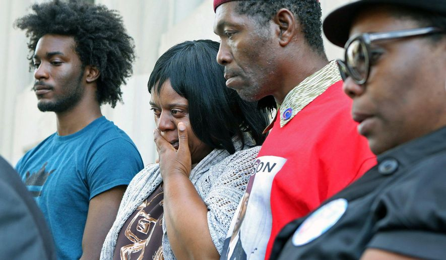 The family of Mansur Ball-Bey listens  on the steps of the Mel Carnahan Courthouse as their lawyer, Jermaine Wooten speaks Thursday, June 2, 2016 in St. Louis. Jennifer Joyce, prosecutor for St. Louis said Thursday she won't be charging two officers in the fatal shooting of a black 18-year-old last year, concluding that no evidence disproves claims by police that it was self-defense. (J.B. Forbes/St. Louis Post-Dispatch via AP)  EDWARDSVILLE INTELLIGENCER OUT; THE ALTON TELEGRAPH OUT; MANDATORY CREDIT