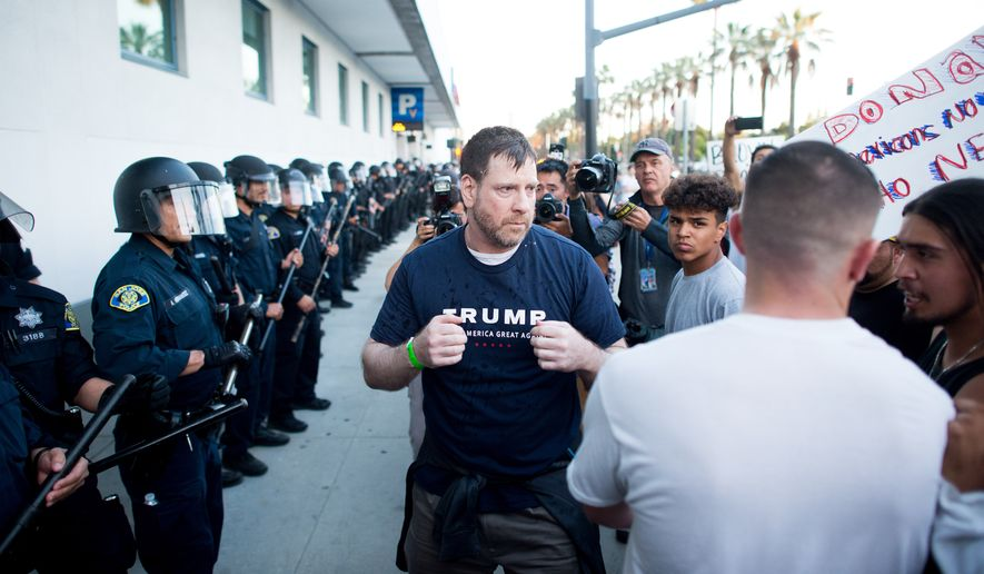 A man leaving a campaign rally for Republican presidential candidate Donald Trump squares off against protesters following him on Thursday, June 2, 2016, in San Jose, Calif. A group of protesters attacked Trump supporters who were leaving the presidential candidate's rally in San Jose on Thursday night. A dozen or more people were punched, at least one person was pelted with an egg and Trump hats grabbed from supporters were set on fire on the ground. (AP Photo/Noah Berger)