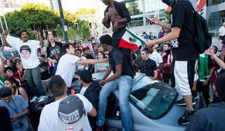 Protesters against Republican presidential candidate Donald Trump climb on a car outside a Trump campaign rally on Thursday, June 2, 2016, in San Jose, Calif. A group of protesters attacked Trump supporters who were leaving the candidate's rally in San Jose on Thursday night. A dozen or more people were punched, at least one person was pelted with an egg and Trump hats grabbed from supporters were set on fire on the ground. (AP Photo/Noah Berger)