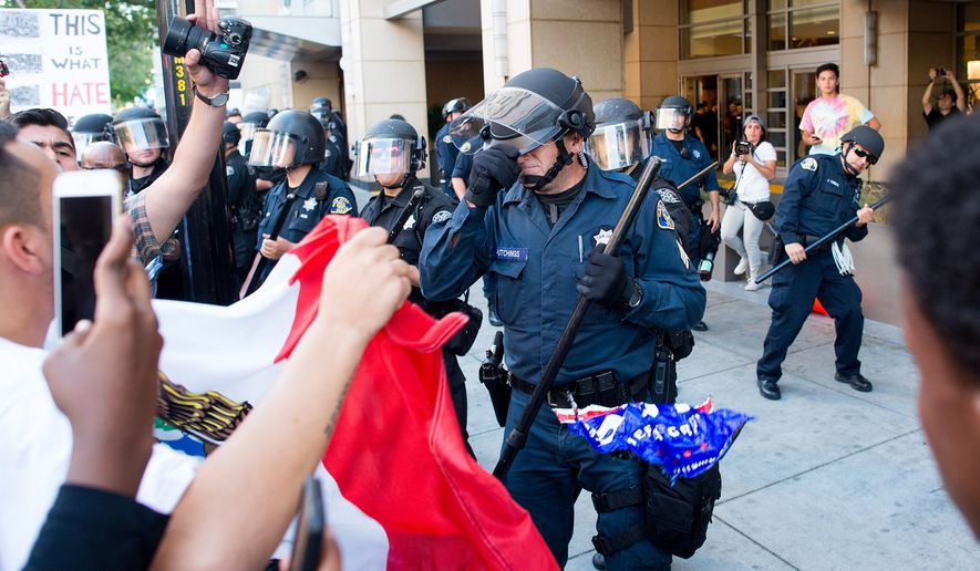 A police officer shields his face as protesters throw objects at officers outside a campaign rally for Republican presidential candidate Donald Trump on Thursday, June 2, 2016, in San Jose, Calif. A group of protesters attacked Trump supporters who were leaving the candidate's rally in San Jose on Thursday night. A dozen or more people were punched, at least one person was pelted with an egg and Trump hats grabbed from supporters were set on fire on the ground. (AP Photo/Noah Berger)