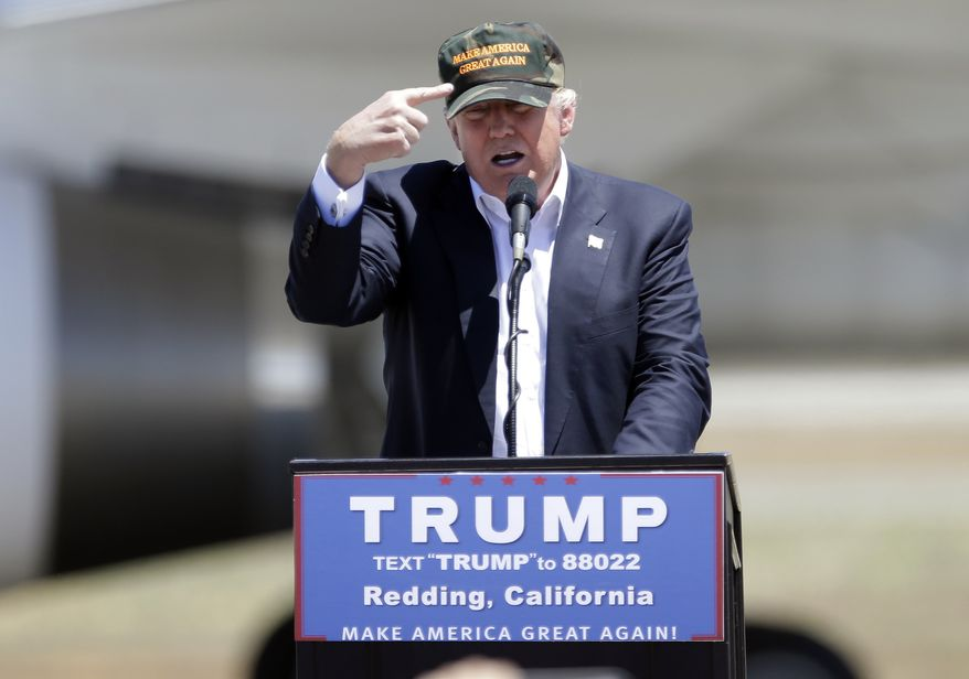 "Republican presidential candidate Donald Trump gestures to a his camouflaged ""Make America Great"" hat as he discuses his support by the National Rifle Association at a campaign rally at the Redding Municipal Airport Friday, June 3, 2016, in Redding, Calif. (AP Photo/Rich Pedroncelli) ** FILE **"