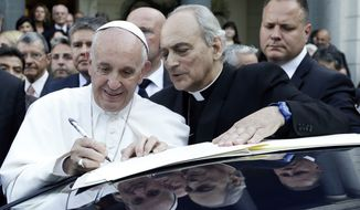 Pope Francis, flanked, by Monsignor Marcelo Sanchez Sorondo signs a declaration during a two-day summit of judges and magistrates against human trafficking and organized crime at the Vatican, Friday, June 3, 2016. Judges and prosecutors from around the world are pledging to crack down on human trafficking and help victims of modern-day slavery in the latest Vatican initiative to draw attention to the problem and rally resources to fight it. (AP Photo/Gregorio Borgia)