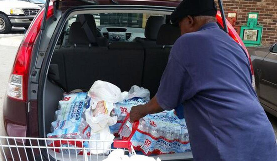 Lee Allen loads bottled water into his vehicle outside the Supervalu Grocery Store in Courtland, Ala., on Friday, June 3, 2016, after a local utility warned residents not to drink the tap water because of chemical contamination. Allen said purchasing water is expensive and inconvenient but necessary after the announcement. (AP Photo/Phillip Lucas)