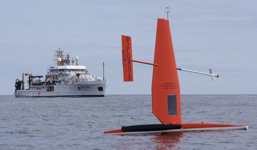 In this April 2015 photo released by NOAA Fisheries, a Saildrone, a 20-foot sailing vessel research platform developed by California-based Saildrone Inc., is tested in the Bering Sea. The National Oceanic and Atmospheric Administration research vessel Oscar Dyson is in the background. Two of the unmanned sailing vessels were launched May 24, 2016, from Dutch Harbor, Alaska, for marine mammal, fish and oceanographic research in the Bering Sea by federal and private researchers. (Mark Frydrych/NOAA Fisheries via AP)