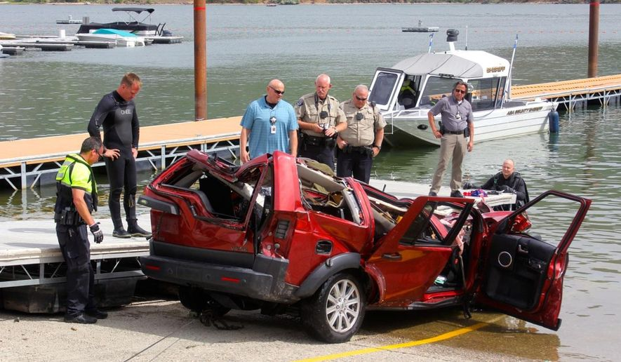In this photo provided by the Ada County Sheriff's Office, Ada County Sheriff's Deputies and the Boise Fire Department dive team stand by the wreckage of an SUV driven by a 40-year-old Boise woman that plunged off a cliff into the Lucky Peak Reservoir Thursday, June 2, 2016, in Boise, Idaho. Divers with the Boise Fire Department recovered the bodies of two girls, ages 12 and 6, and the body of a 10-year-old boy from the vehicle, which was about 40 feet below the surface Thursday morning, according to the Ada County Sheriff's Office. A witness saw the SUV accelerate from the side of the road to go over the cliff, the sheriff's office said. (Patrick Orr/Ada County Sheriff's Office via AP)