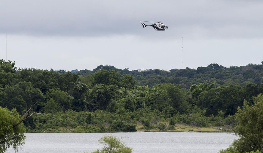 A Texas DPS helicopter flies over Lake Belton near the scene of an accident at Fort Hood at Owl Creek Park near Gatesville, Texas, on Thursday, June 2, 2016. Fort Hood says several soldiers are dead and six are missing after an Army troop truck was washed from a low-water crossing and overturned in a rain-swollen creek at Fort Hood in Central Texas. (Michael Miller/The Temple Daily Telegram via AP)