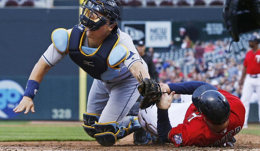 The face mask ofTampa Bay Rays catcher Hank Conger gets twisted as Minnesota Twins' Joe Mauer beats the tag to score on a single by Trevor Plouffe in the third inning of a baseball game Friday, June 3, 2016, in Minneapolis. (AP Photo/Jim Mone)