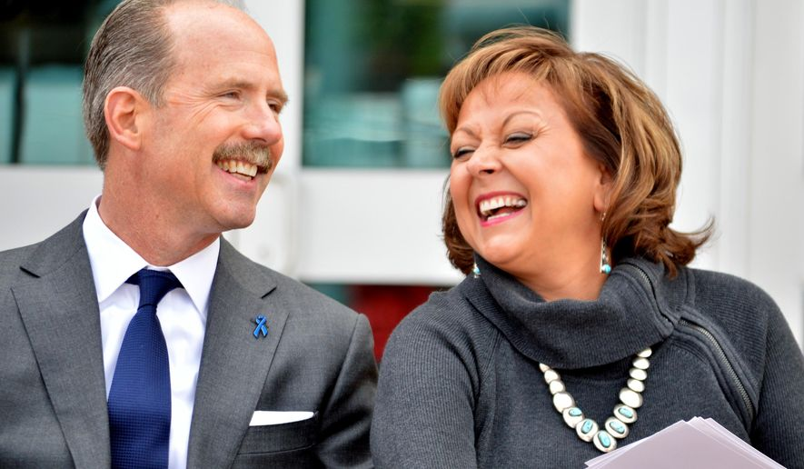 Albuquerque Mayor Richard Berry, left, and New Mexico Gov. Susana Martinez, right, laugh during a press conference in Albuquerque on Wednesday, June 1, 2016. Martinez, the nation's only Latino governor, said Wednesday she won't support Libertarian presidential candidate and former New Mexico Gov. Gary Johnson because of his promise to reduce military forces and his stance to legalize marijuana. (AP Photo/Russell Contreras)