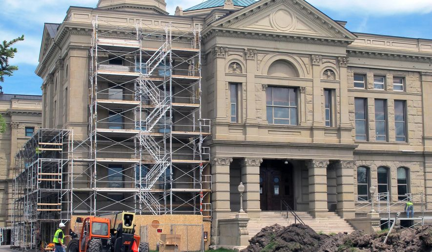 Workers erect scaffolding at the Wyoming State Capitol in Cheyenne, on Friday, June 3, 2016. State officials are defending against lawsuits challenging how the state issued contracts for the ongoing restoration work. (AP Photo/Ben Neary)