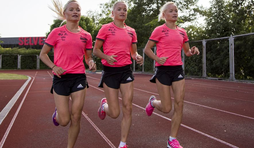 In this photo taken on Thursday, June 2, 2016, Estonian athletes sisters Lily Luik, left, Liina Luik, center, and Leila Luik attend a training session after an interview with The Associated Press at a track in Estonia. The 30-year-old sisters will be the first triplets to compete in the Olympics, all of them running in the women's marathon, and say they are used to judges getting them mixed up in events. (AP Photo/Vitnija Saldava)
