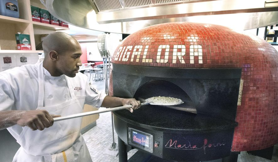 Chef Taj Caver puts a  thin crust prosciutto pizza into the huge oven at Wood Fired Bigalora Cucina in the A Terminal on May 16, 2016 at Detroit Metropolitan Airport in Romulus, Mich. The airport a place where one can buy $10,000 watches, eat gourmet pizza from a $40,000 oven imported from Italy or sip on wine stored in state-of-the-art, temperature-controlled cases. All while enjoying the stylings of musicians on two baby grand pianos. (Daniel Mears/Detroit News via AP)  DETROIT FREE PRESS OUT; HUFFINGTON POST OUT; MANDATORY CREDIT