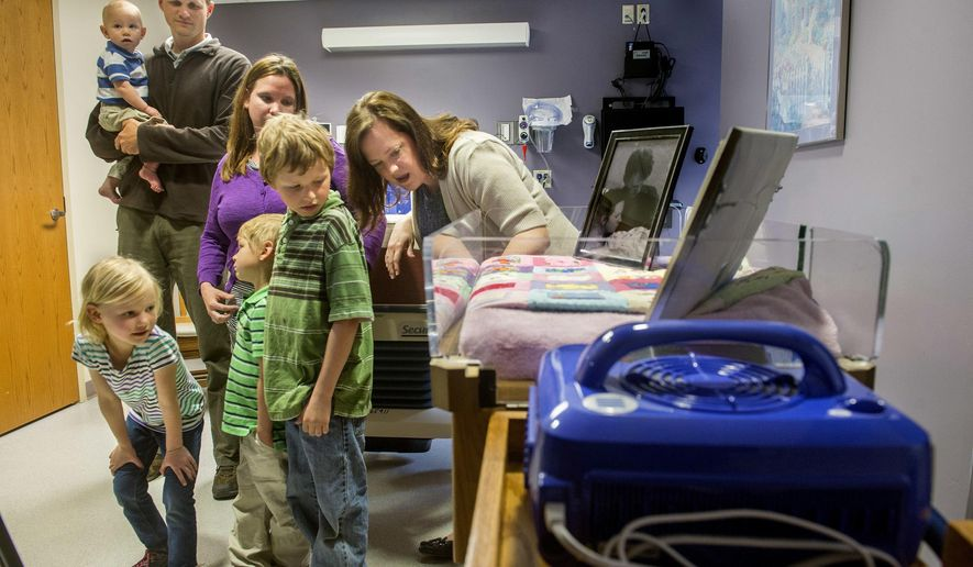 In this May 9, 2016 photo, Kyler Lange, left, leans in to listen as Sarah Greer, of the OSF St. Francis Medical Center Perinatal Supportive Care in Peoria, Ill., talks to her and her brothers, Weston, foreground, Dean, and Quintin, and their parents Aaron and Terra Lange, about the CuddleCot the family donated to the OSF Family Birthing Center. The CuddleCot is a specialized cooling device fitted for use in a bassinet that allows families to spend more time with a baby who is stillborn or dies shortly after birth. The Lange family had a daughter stillborn in March 2014. (David Zalaznik/Journal Star via AP) MANDATORY CREDIT
