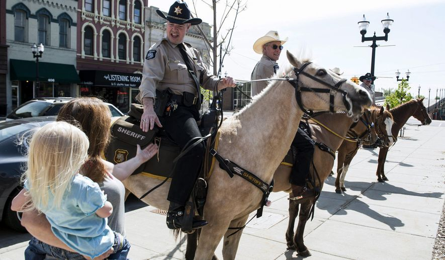 ADVANCE FOR RELEASE MONDAY, JUNE 6, 2016, AT 12:01 A.M. EDT. AND THEREAFTER - In this May 20, 2016 photo, Saginaw County sheriff William Federspiel greets passers-by with deputies on horseback in Old Town Saginaw, Mich. Federspiel and multiple deputies from his office's Mounted Division, or posse, turned a few heads and drew a crowd when they came trotting up Court near Michigan that morning, The Saginaw News reported. (Jacob Hamilton/The Saginaw News via AP) ALL LOCAL TELEVISION OUT; LOCAL TELEVISION INTERNET OUT; MANDATORY CREDIT