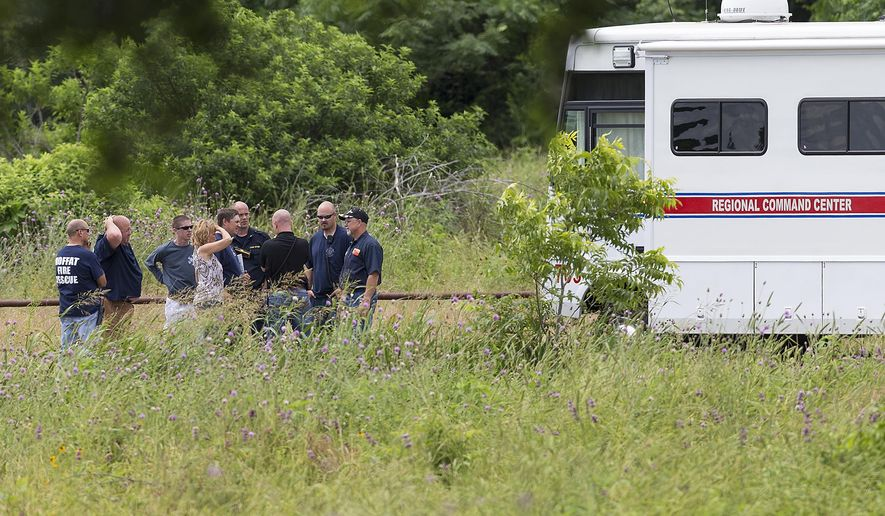 Emergency responders talk near the scene of an accident at Fort Hood at Owl Creek Park near Gatesville, Texas, on Thursday, June 2, 2016. Fort Hood says several soldiers are dead and six are missing after an Army troop truck was washed from a low-water crossing and overturned in a rain-swollen creek at Fort Hood in Central Texas. A statement from the Texas Army post says the accident happened about 11:30 a.m. Thursday in an area near Cold Springs and Owl Creek. (Michael Miller/The Temple Daily Telegram via AP) MANDATORY CREDIT