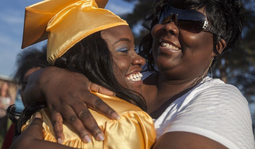 Jewel Lee  hugs her mother LaShawn Williams after receiving her diploma at the Arthur Hill High Commencement ceremony on Thursday, June 2, 2016 in Saginaw, Mich. In 2009, Leewas struck in the head by a bullet while waiting on the porch to have her hair braided for church. She survived the shooting and then spent years rehabilitating and working toward her goal of finishing school.  (Josie Norris/The Saginaw News via AP) ALL LOCAL TELEVISION OUT; LOCAL TELEVISION INTERNET OUT; MANDATORY CREDIT