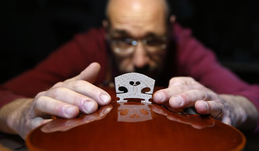 Violinmaker Marco Brunelli, 43, was born in Rochester, Minnesota, United States, checks the shape of a violin inside his lab in Pavia, Italy, Friday, April 15, 2016. Here, in the quiet pedestrian streets of Pavia, is Marco Brunello's instrument boutique. A few examples of his work are on display in the window, but the magic happens in the shop's back room, the instrument-making lab. (AP Photo/Antonio Calanni)