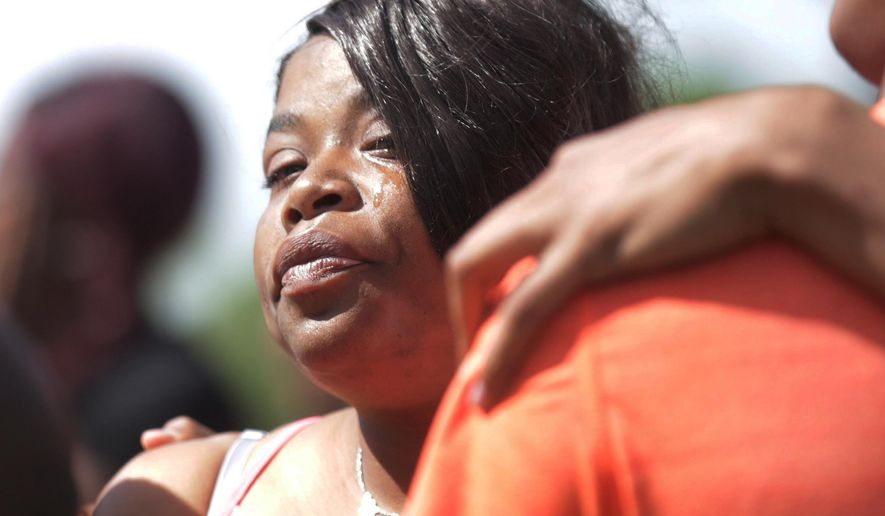 Crystal Mitchell, the mother of Deontae Mitchell is comforted by family and friends when she arrives where a body has been found, Thursday, June 2, 2016 in Detroit.  Detroit Police Chief James Craig said the medical examiner will determine whether the body found in a field is Deontae Mitchell, who disappeared Tuesday night.  (Regina H. Boone/Detroit Free Press via AP)  DETROIT NEWS OUT; TV OUT; MAGS OUT; NO SALES; MANDATORY CREDIT DETROIT FREE PRESS