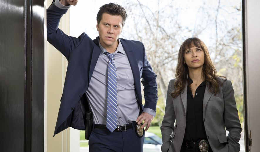 "This image released by TBS shows, Hayes MacArthur, left, and Rashida Jones from the series, ""Angie Tribeca."" (Tyler Golden/TBS via AP)"