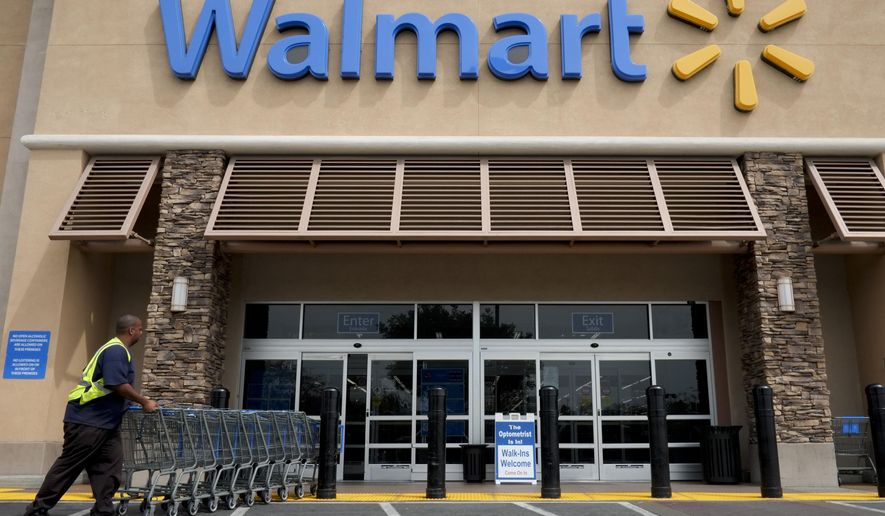 FILE - In this May 9, 2013 file photo, a worker pushes shopping carts in front of a Wal-Mart store in La Habra, Calif. Wal-Mart Stores Inc. says it will be testing its grocery delivery service with ride-hailing companies Uber and Lyft in the next two weeks in Denver and Phoenix. That's in addition to a quiet pilot program that started in March 2016 with Deliv for its Sam's Club customers that involves delivery of general merchandise and grocery for business members in Miami.  (AP Photo/Jae C. Hong, File)
