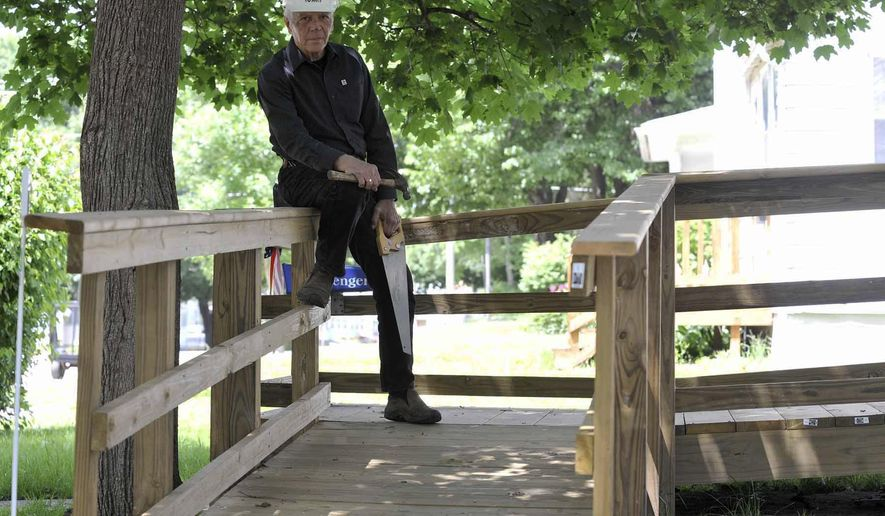 In this Thursday, June 2, 2016 photo, Howard Hartman, executive director of the Twin Rivers Habitat for Humanity, poses on a recently constructed handicap ramp at a home in Fort Dodge, Iowa. The group will soon be adding the construction of ramps to their projects in Humboldt and Webster Counties.  (Hans Madsen /The Messenger via AP) MANDATORY CREDIT