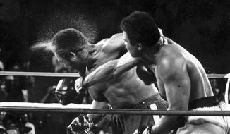 George Foreman takes a right to the head from challenger Muhammad Ali in the seventh round in the match dubbed Rumble in the Jungle in Kinshasa, Zaire, Oct. 30, 1974. Ali, the magnificent heavyweight champion whose fast fists and irrepressible personality transcended sports and captivated the world, has died June 3, 2016. He was 74. (AP Photo/Ed Kolenovsky) ** FILE **