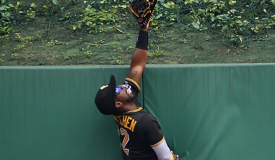 Pittsburgh Pirates center fielder Andrew McCutchen climbs the center field wall but can't make the catch on a solo home run by Los Angeles Angels right fielder Kole Calhoun off Pirates starting pitcher Jeff Locke during the first inning of a baseball game in Pittsburgh, Saturday, June 4, 2016. (AP Photo/Gene J. Puskar) **FILE**