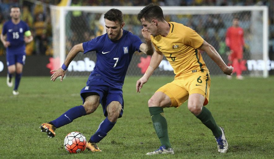 Greece's Ioannis Gianniotas, left, takes the ball behind Australia's Milos Degenek during their soccer friendly in Sydney, Australia, Saturday, June 4, 2016. (AP Photo/Rob Griffith)