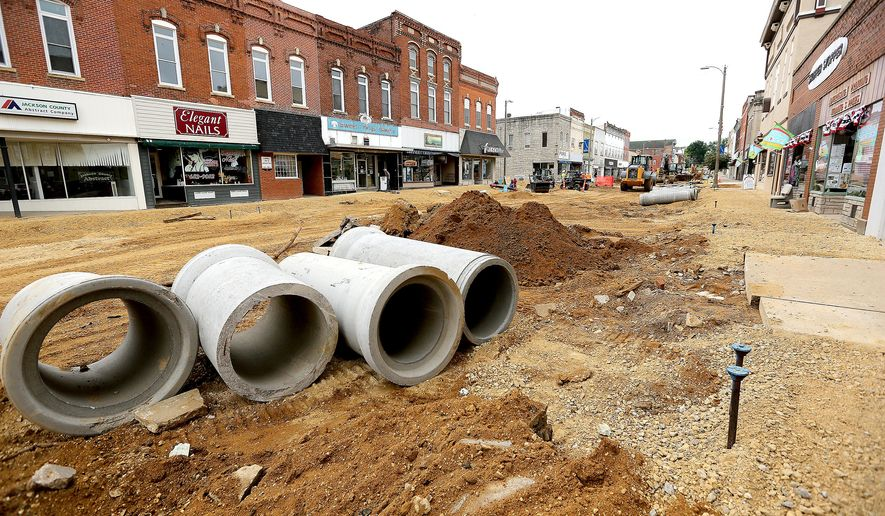 ADVANCE FOR USE SATURDAY, JUNE 4 - In this photo taken, Friday, May 27, 2016, work continues on major road project that includes Main Street in Maquoketa, Iowa. The $3.7 million reconstruction project includes new water and sewer mains, storm sewers and concrete paving. It also will feature new streetscape amenities, such as benches, planters, vintage brickwork and streetlights. (Dave Kettering/Telegraph Herald via AP) MANDATORY CREDIT