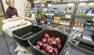 Jan DeMoure, right, looks at a checklist while shopping on Wednesday, May 18, 2016, at the Food Equality Initiative with the assistance of food bank manager, Karen Miller, at the New Haven Seventh-Day Adventist Church in Overland Park, Kansas. The food pantry serves families, like Demoure,  coping with the high costs of food safe for children with food allergies or Celiac disease. (Allison Long/The Kansas City Star via AP/File) MANDATORY CREDIT