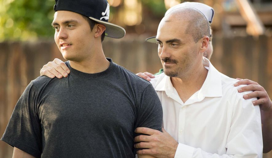 In this Friday, June 3, 2016 photo, Weldon Angelos, right, holds his son Anthoney in Sandy, Utah. Weldon Angelos, a Utah music producer who was ordered to 55 years behind bars for bringing guns to marijuana deals has been set free, after 12 years in prison and national outcry over the mandatory minimum sentencing laws that forced a federal judge to impose the lengthy term. (Rick Egan/The Salt Lake Tribune via AP) DESERET NEWS OUT; LOCAL TELEVISION OUT; MAGS OUT; MANDATORY CREDIT