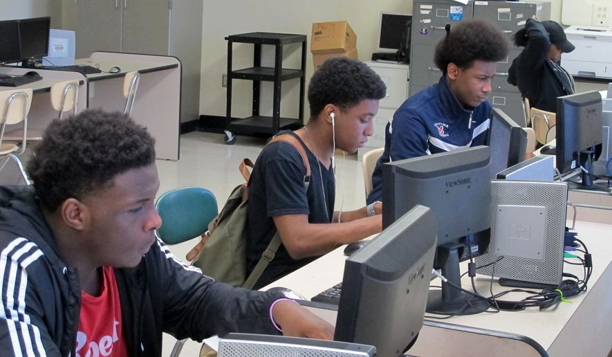In this May 24, 2016 photo, students work at computers inside Bennett High School in Buffalo, N.Y. The school is one of five troubled high schools being redesigned with a focus on specialty programming, such as computer science or solar energy. The goal is to position students to land well-paying jobs being created amid a surge in economic development in the city. (AP Photo/Carolyn Thompson)