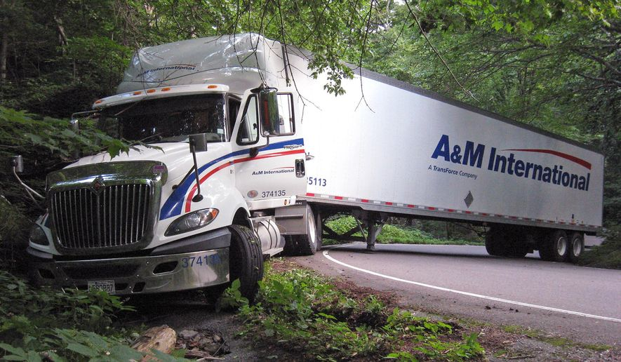 --HOLD FOR RELEASE, JUNE 4TH-- In this August 18, 2015 photograph provided by the Vermont Dept. of Motor Vehicles, a tractor trailer truck blocks the road and ends up stuck in the Smugglers Notch portion of Vermont Route 108, known for its tight turns as it rises through a mountain pass, in Cambridge, Vermont. State officials say truckers regularly ignore the signs when following their GPSs and get stuck. Starting July 1 truckers who get stuck are facing fines of up to $2,000 for a first offense. (Christopher Lynch, Vermont Dept. of Motor Vehicles via AP)