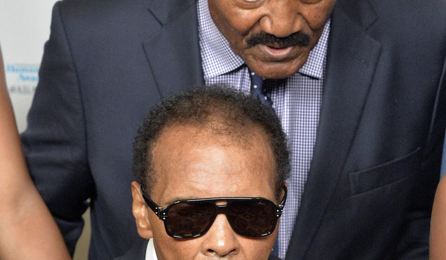 """FILE - In this Sept. 27, 2014, file photo, Jim Brown, rear, whispers a message to Muhammad Ali during their meeting before the Ali Humanitarian Awards ceremony, in Louisville, Ky. The message that Brown whispered was """"You're the greatest of all time,"""" Brown later told a reporter. Ali, the magnificent heavyweight champion whose fast fists and irrepressible personality transcended sports and captivated the world, has died according to a statement released by his family Friday, June 3, 2016. He was 74.  (AP Photo/Timothy D. Easley, File)"""