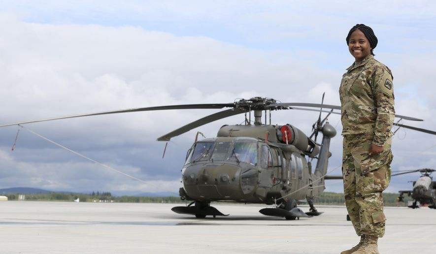ADVANCE FOR WEEKEND JUNE 4-5 2016 AND THEREAFTER - In this May 26, 2016 photo, Spc. Brittany Cobb-Lyttle stands in front of a Black Hawk helicopter on Ladd Army Airfield at Fort Wainwright in Fairbanks, Alaska. (Erin Corneliussen/Fairbanks Daily News-Miner via AP)
