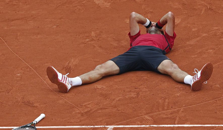 Serbia's Novak Djokovic celebrates winning the final of the French Open tennis tournament against Britain's Andy Murray in four sets 3-6, 6-1, 6-2, 6-4, at the Roland Garros stadium in Paris, France, Sunday, June 5, 2016. (AP Photo/Christophe Ena)
