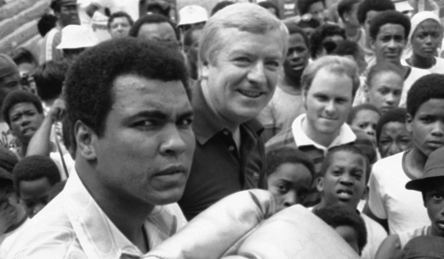 """Muhammad Ali frowns for the benefit of cameramen on Tuesday, August 16, 1978, during a news conference at his Deer Lake, Pennsylvania Camp. Giant-size glove he wears bears autographs.   On a more serious note, Ali told newsmen that the thought """"...just four more weeks,"""" rolls around in his head like a stuck phonograph needle. The four weeks, of course, refers to the September 15 date he has with Leon Spinks in New Orleans. That's when Ali expects to redeem his humiliating defeat of six months ago, when he lost his title to Spinks. (AP Photo/David Pickoff)"""