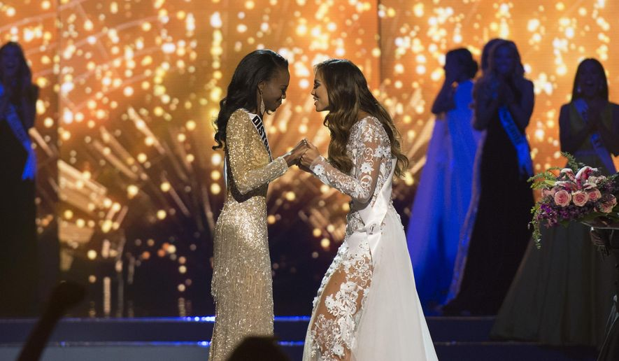 Finalists Miss District of Columbia, Deshauna Barber, left, and Miss Hawaii, Chelsea Hardin, wait for the results during the 2016 Miss USA pageant in Las Vegas, Sunday, June 5, 2016. (Jason Ogulnik/Las Vegas Review-Journal via AP) LOCAL TELEVISION OUT; LOCAL INTERNET OUT; LAS VEGAS SUN OUT