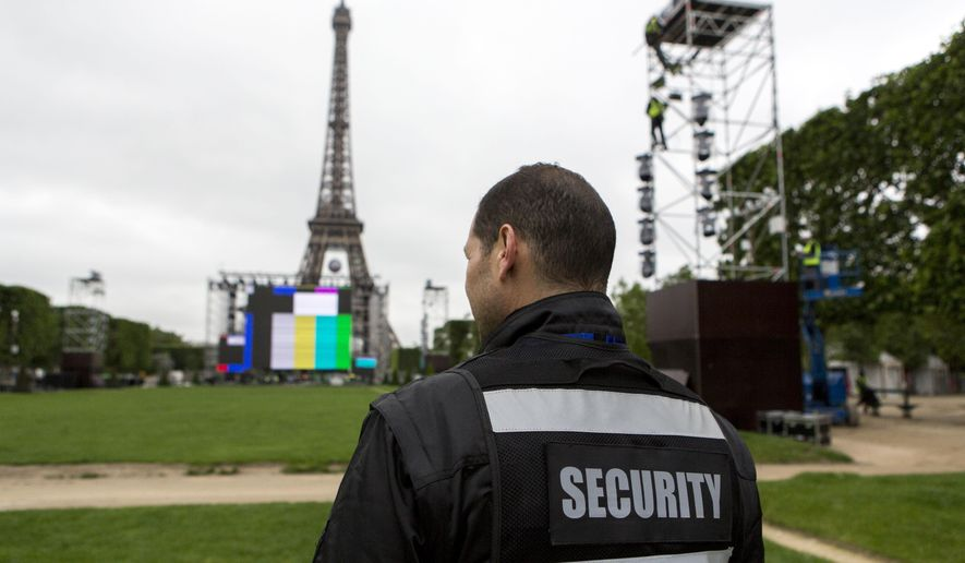 A security guard looks at the Euro 2016 fan zone, under construction on the Champs de Mars in Paris, Friday, June 3, 2016. France's interior minister says the Paris police chief wants more security staff to protect fans at the 2016 European Championship, which starts next week. (AP Photo/Kamil Zihnioglu)