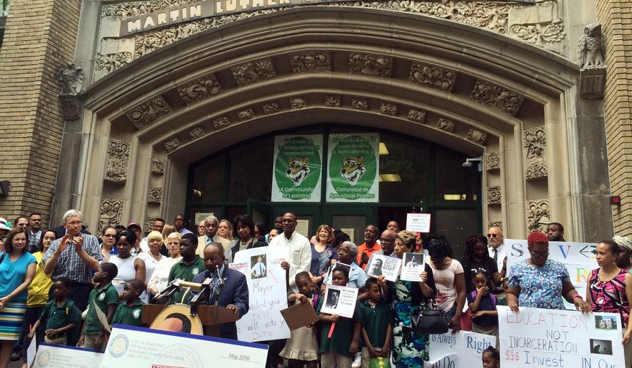 In this June 1, 2016 photo, advocates, parents and students attend a rally outside the Martin Luther King Jr. Elementary School in Hartford, Conn., to protest a proposal to relocate students to another building. The plan to move students from the decaying Hartford schoolhouse to a neighboring building's lower level is stirring cries of discrimination in the predominantly African-American neighborhood. (AP Photo/Michael Melia)