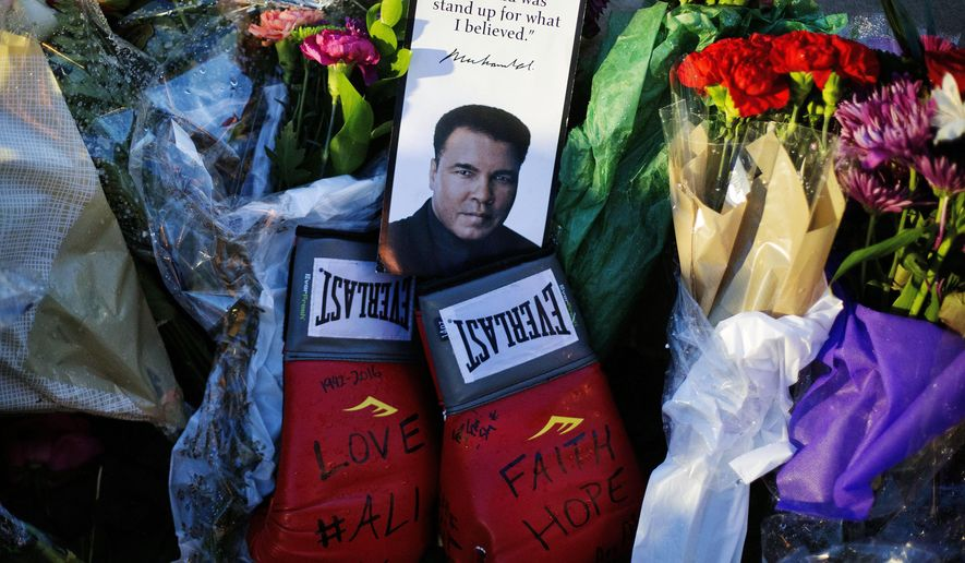 Boxing gloves and a message sit among flowers at a makeshift memorial to Muhammad Ali at the Muhammad Ali Center, Saturday, June 4, 2016, in Louisville, Ky. Muhammad Ali died Friday at age 74. (AP Photo/David Goldman)